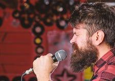 Muzyk z brody i wąsy śpiewacką piosenką w karaoke Punk rock pojęcie Mężczyzna z spiętą twarzą trzyma mikrofon zdjęcie royalty free