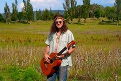 Muzyka hipisa młodzi człowiecy z gitarą Fotografia Stock