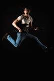 Muzyka i twórczość Przystojny młody człowiek w koszulce i cajgach skacze z gitarą elektryczną na czarnym odosobnionym tle, Fotografia Royalty Free