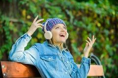 Muzyka jest tak dużo zabawą nowożytna technologia zamiast czytania Relaksuje w parku modniś dziewczyna z odtwarzacz mp3 słuchał m obrazy royalty free