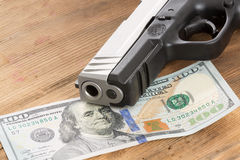 Muzzle of a gun with a 100 dollar bill. Close up of the muzzle of a gun with a 100 American dollar bill lying on a wooden table in a conceptual image of crime Royalty Free Stock Image