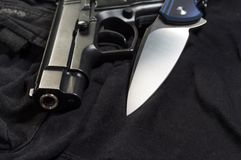 Muzzle pistol and knife blade. Weapon close-up royalty free stock photo