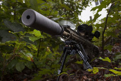 Muzzle side. Silencer on a rifle seen from the front in some trees Stock Image