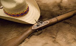 Muzzleloader and Hat. Old Muzzleloader and Hat with a colorful mayan band on top of an old deer skin royalty free stock photos