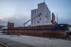 MV Kine loads grain. Image is shot at Halden, Norway grain silo and shows MV Kine which loads grain. MV Kine sailing under the Bahamas flag Stock Photography