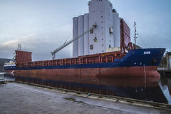 MV Kine loads grain. Image is shot at Halden, Norway grain silo and shows MV Kine which loads grain. MV Kine sailing under the Bahamas flag Royalty Free Stock Image