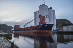 MV Kine loads grain. Image is shot at Halden, Norway grain silo and shows MV Kine which loads grain. MV Kine sailing under the Bahamas flag Stock Photos