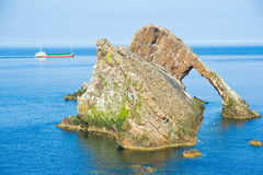 MV Scot Explorer sails past the Bowfiddle rock. The Bowfiddle rock with Scotline's MV Scot Explorer sailing past on a wonderfully calm day Royalty Free Stock Photography