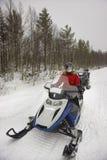 Móvil de manejo de la nieve de la mujer en Ruka de Laponia Foto de archivo