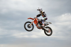 MX de raceauto voert een sprong op achtergrond van wolken uit Stock Foto