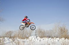 MX driver on the motorcycle is flying over the hill snow Royalty Free Stock Image
