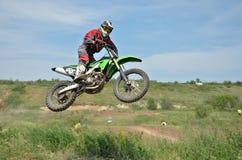 MX-Mitfahrer fliegt durch die Luft Stockfotografie