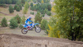 MX moto cross racing - Girl Bike Rider rides on a dirt motorcycle - extreme jump. Telephoto stock image