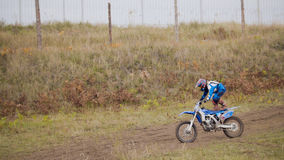 MX moto Girl Biker shows acrobatic at cross racing - rider on a dirt motorcycle. Telephoto stock photography
