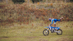 MX moto woman Biker shows acrobatic at cross racing - rider on a dirt motorcycle. Telephoto royalty free stock image