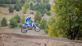 Mx-motokors som springer - flickacykelryttaren rider på en smutsmotorcykel - extremt hopp Fotografering för Bildbyråer