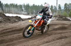 MX motorcycle with rider shoots out of a turn Stock Photos