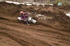 MX racer, with a large slope in gritty point-blank rotates on th Stock Photography