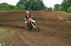 MX racer on a motorbike accelerating. Мotorcycle racer on a motorbike accelerating on a sandy track Stock Photo