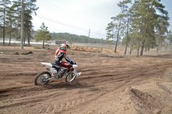 MX racer on the motorcycle accelerates on a straight section san Stock Images
