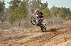 MX racer standing in motion performed a wheelie Stock Photos