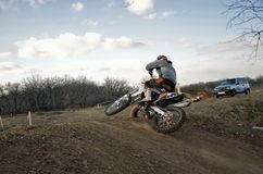 MX rider on dike rides mound performs scrub Royalty Free Stock Photo
