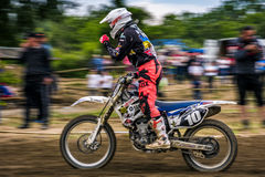 MX rider finish the race. Motion blur with flying dirt Royalty Free Stock Photos