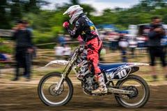 MX rider finish the race. Motion blur with flying dirt. Uzhgorod, Ukraine - May 21, 2017: MX rider Finish the race. Motion blur with flying dirt. TransCarpathian Royalty Free Stock Photos
