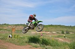 MX rider on the motorbike takes off from the hill Stock Photography