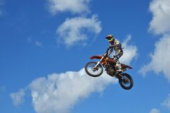 MX rider on the motorbike takes off from the hill Stock Image