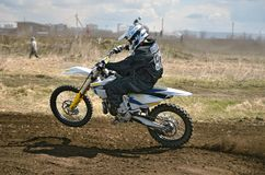 MX rider on a motorcycle in a bend. MX racer on a motorbike acceleration out bend on track motocross stock photography