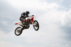 MX rider soaring flight with a turn of wheel bike. MX rider soaring flight with a turn of the wheel motocross bike, on a background of white clouds royalty free stock photo