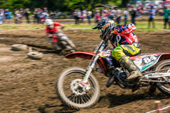 MX rider turns in a dirt. Motion blur with flying dirt. MX rider turns on a corner. Motion blur with flying dirt. TransCarpathian regional Motocross Championship royalty free stock image