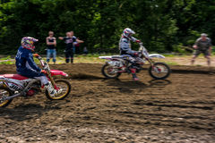 MX rider turns in a dirt. Motion blur with flying dirt Royalty Free Stock Image