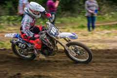 MX rider turns in a dirt. Motion blur with flying dirt Royalty Free Stock Photos