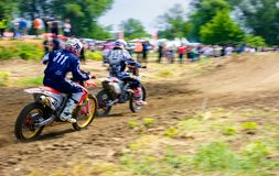 MX rider turns in a dirt. Motion blur with flying dirt. Uzhgorod, Ukraine - May 21, 2017: MX rider turns on a corner. Motion blur with flying dirt Stock Photography