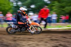 MX rider turns in a dirt. Motion blur with flying dirt. Uzhgorod, Ukraine - May 21, 2017: MX rider turns on a corner. Motion blur with flying dirt stock image