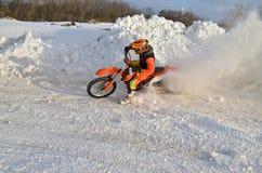 MX-Winter, Drehung mit Nachdruck in einem Schneewehenrennläufer Stockbilder