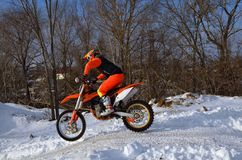 MX winter motocross racer on a motorcycle arrives on a snowy hil Royalty Free Stock Images