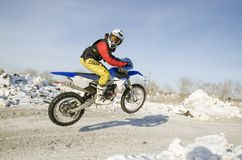 MX winter rider soars from a hill looking back Royalty Free Stock Photography