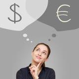 Myśląca biznesowa kobieta przyglądająca up na dolarowej i euro walucie Fotografia Royalty Free