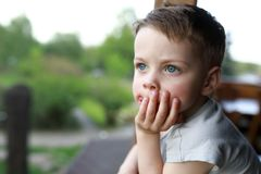 Myśląca chłopiec przy tarasem Obrazy Royalty Free