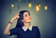 Myśląca młoda kobieta przyglądająca przy dolarowych pomysł żarówek above głową up obraz stock