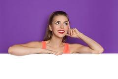 Myśląca Piękna dziewczyna Opierająca się Na plakacie Fotografia Stock