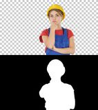 Myśląca pracownik budowlany kobieta jest ubranym budowniczego hełm, Alfa kanał obrazy stock