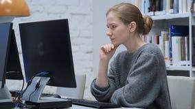 Myśląca rudzielec kobieta pracuje na laptopie, siedzi w biurze zdjęcia stock