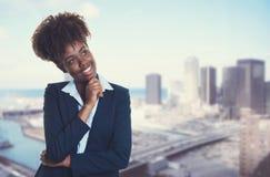 Myślący amerykanina afrykańskiego pochodzenia bizneswoman z linią horyzontu miasto zdjęcia stock