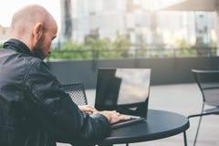 Myślący atrakcyjny dorosły pomyślny łysy brodaty mężczyzna w czarnej kurtce z laptopem w ulicznej kawiarni przy miastem obrazy royalty free
