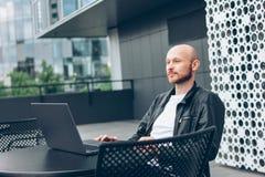Myślący atrakcyjny dorosły pomyślny łysy brodaty mężczyzna w czarnej kurtce z laptopem w ulicznej kawiarni przy miastem obrazy stock