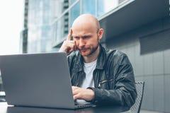 Myślący atrakcyjny dorosły pomyślny łysy brodaty mężczyzna w czarnej kurtce z laptopem w ulicznej kawiarni przy miastem obraz stock
